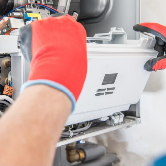 Boiler being repaired with red gloves | Boiler Repair Leicester | Boiler Servicing