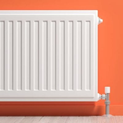 Warm radiator on orange wall - coalville plumber